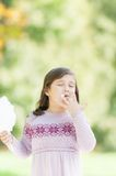 Beautiful little girl eating cotton candy in park. Stock Photo