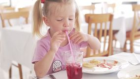 Beautiful little girl eating french fries with ketchup in a cafe stock footage