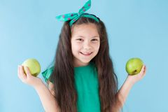 Beautiful little girl eating a Green Apple fruit royalty free stock photography