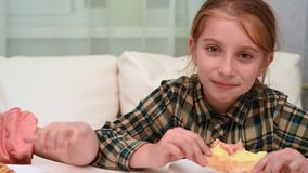 Beautiful little girl eating pizza and waving her hand stock footage
