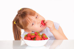 Beautiful little girl eating strawberries Stock Photo