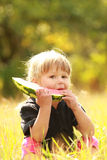 Beautiful little girl eating watermelon on the nature Stock Photos