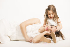Beautiful little girl embracing her mother on white background. Happy family concept. Mother and her little lovely daughter, concept of togetherness, studio shot Stock Photo