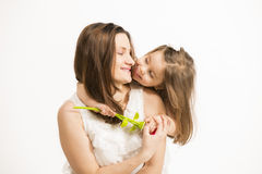Beautiful little girl embracing her mother on white background. Happy family concept. Mother and her little lovely daughter, concept of togetherness, studio shot Stock Images