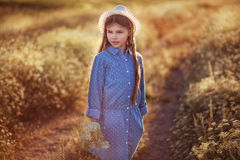 Beautiful little girl enjoing sunset in the field of flowers. Beautiful little girl enjoing sunset in the field Royalty Free Stock Photography