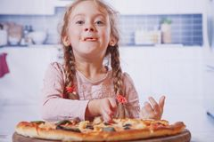 Beautiful little girl enjoying a delicious pizza in nature food