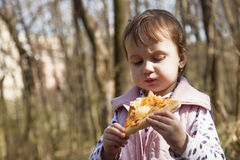 Beautiful little girl enjoying a delicious pizza in nature food stock images