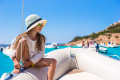 Beautiful little girl enjoying sailing on boat in Stock Images
