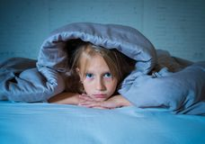Beautiful little girl feeling sad and tired not being able to sleep at night covering head under duvet royalty free stock image