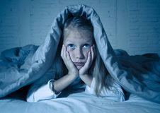 Beautiful little girl feeling sad and tired not being able to sleep at night covering head under duvet royalty free stock photo