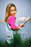 Beautiful little girl fishing. Beautiful little girl playing with  fishing stick Royalty Free Stock Photos