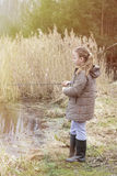 Beautiful little girl fishing with spinning on the river stock photos