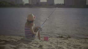 Beautiful little girl fishing with spinning rod stock video