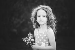 Beautiful little girl with a flower in her hand. Black and white Stock Photography