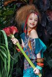 A beautiful little girl with flower wearing native costume in the jungle or rainforest. Stock Images