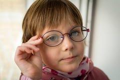 Beautiful little girl with fogged eyeglasses Stock Image