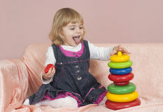 Beautiful little girl folding pyramid Stock Image