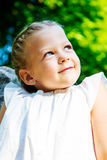 Beautiful little girl in forest. looking up Stock Images