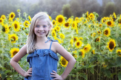Beautiful little girl in front of sunflower field Royalty Free Stock Photos