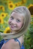 Beautiful little girl in front of sunflower field stock photo