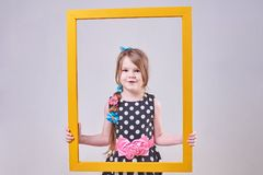 Beautiful little girl, with a funny expression on his face, holding a yellow frame royalty free stock images