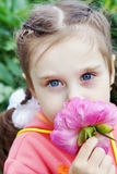 Beautiful Little Girl in a Garden Sniffs Flower Stock Images
