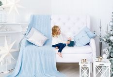 Beautiful little girl with gift box sitting on sofa in white room. Christmas interior stock photo