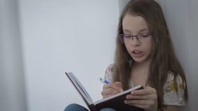 Beautiful little girl in glasses diligently does his homework at window. stock video