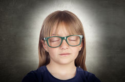 Beautiful little girl with glasses and her eyes closed. On a over gray background Royalty Free Stock Photo