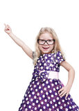 Beautiful little girl in glasses showing on something by finger Royalty Free Stock Photo
