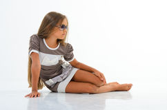 Beautiful little girl with glasses in the studio. Stock Photo
