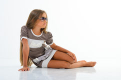 Beautiful little girl with glasses in the studio. Stock Photos