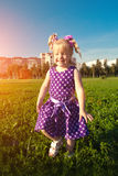 Beautiful little girl on the grass in the park. Smiling child on. Cute little girl  on the grass in the park. Smiling nice child on a field with Royalty Free Stock Images