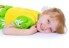 Beautiful little girl in a green dress with daisies, lies in a c Royalty Free Stock Photography
