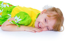 Beautiful little girl in a green dress with daisies, lies in a c Stock Photos