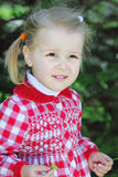 Beautiful little girl on a green meadow in a beautiful red dress Royalty Free Stock Photo