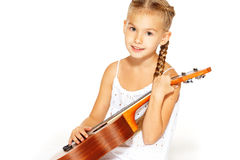 Beautiful little girl with a guitar. A beautiful little girl with a charming smile in a white dress with a guitar Stock Photos