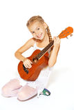 Beautiful little girl with a guitar. A beautiful little girl with a charming smile in a white dress with a guitar Royalty Free Stock Images