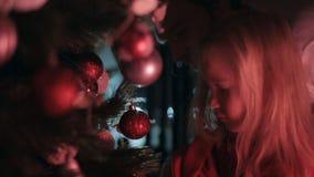 Beautiful little girl hangs on the Christmas tree stock video footage