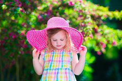 Beautiful little girl in a hat in blooming summer garden Royalty Free Stock Photos