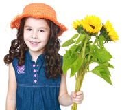 Beautiful little girl in a hat and holding flowers Stock Image