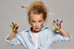 Beautiful little girl with a painted fingers is posing on a gray background. Beautiful little girl having a brush in her chic curly blond hair, wearing in a royalty free stock photography