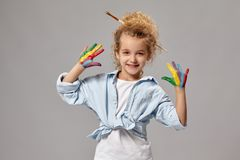 Beautiful little girl with a painted fingers is posing on a gray background. Beautiful little girl having a brush in her chic curly blond hair, wearing in a stock photography