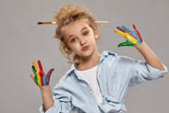 Beautiful little girl with a painted fingers is posing on a gray background. Beautiful little girl having a brush in her chic curly blond hair, wearing in a royalty free stock photo