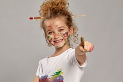 Beautiful little girl with a painted fingers is posing on a gray background. Beautiful little girl having a brush in her chic curly blond hair, wearing in a royalty free stock images