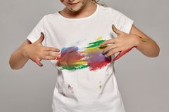 Beautiful little girl with a painted fingers is posing on a gray background. Beautiful little girl having a chic curly blond hair, wearing in a white t-shirt stock image