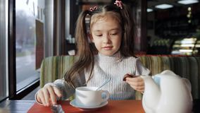 Beautiful little girl is having lunch in a cafe. baby girl eats candy and flavored tea stock video footage