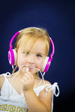 Beautiful little girl with headphones on her ears Stock Photography