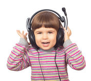 Beautiful little girl in headphones listening to music Stock Image