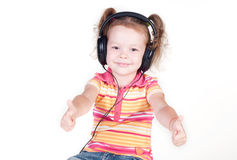 Beautiful little girl with headphones showing thumbs up Royalty Free Stock Image